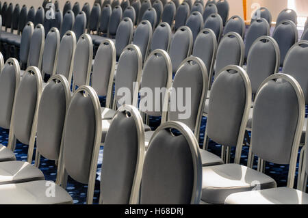 Grey chairs lined up for a conference in a large hall - Stock Photo