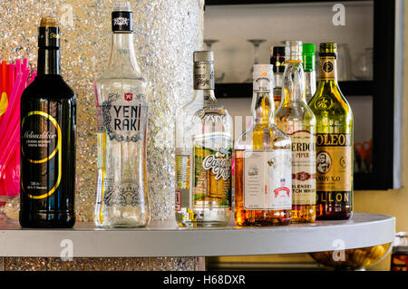Spirits, including Raki, Vodka, Brandy, Scotch Whiskey, on the shelf of a bar in a Turkish all-inclusive hotel. - Stock Photo
