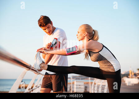 Young couple exercising and stretching muscles before sport activity at the pier - Stock Photo