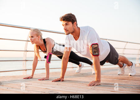 Young sports woman and man doing plank exercise together outdoors at the pier - Stock Photo