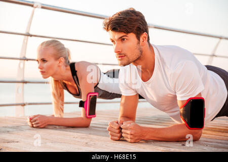 Close up of a young sports woman and man doing plank exercise together outdoors at the pier - Stock Photo