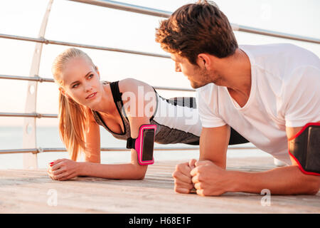Close up of a young fitness woman and man doing plank exercise together outdoors at the pier - Stock Photo