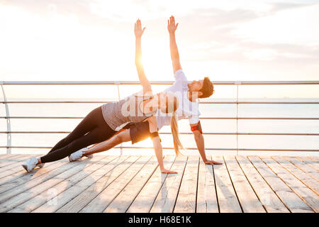 Smiling couple doing yoga exercises outdoors at the beach pier - Stock Photo