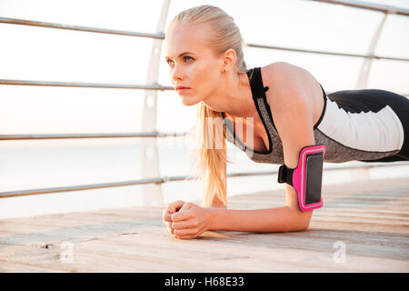 Fitness woman doing planking yoga exercises outdoors at the beach pier - Stock Photo