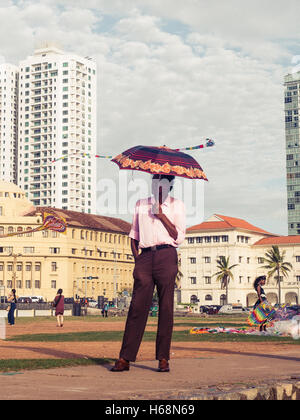Colombo, Sri Lanka. June 10th 2016. A man stood under an umbrella at Galle Face Green, Sri Lanka. - Stock Photo