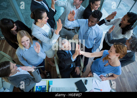 Businesspeople giving high five to each other - Stock Photo