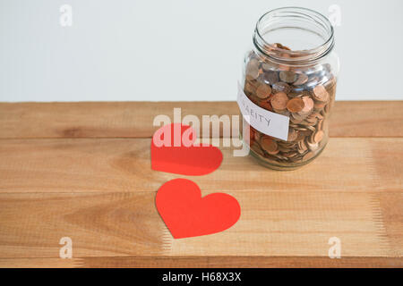 Close-up of coins in bottle and heart - Stock Photo