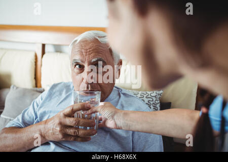 Nurse giving a glass of water to senior man - Stock Photo