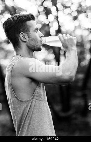 Young athlete drinking water in park.black and white photo - Stock Photo