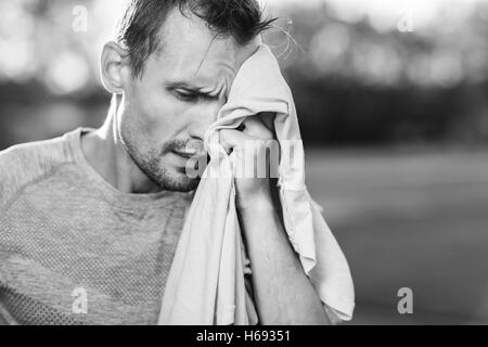 Black and white portrait of tired man wiping with towel - Stock Photo