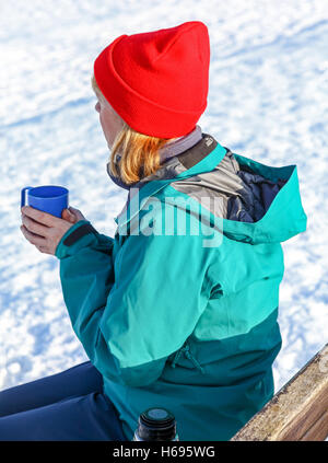 A woman sitting outside in the snow drinking a hot drink and warming her hands on a mug of tea or coffee - Stock Photo
