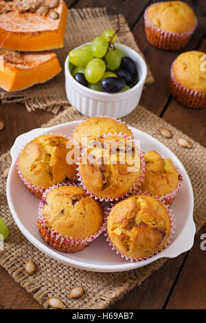 Appetizing and ruddy muffins with pumpkin and grapes - Stock Photo
