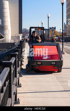 A city worker riding a sidewalk sweeper in downtown Ottawa, Ontario, Canada. - Stock Photo