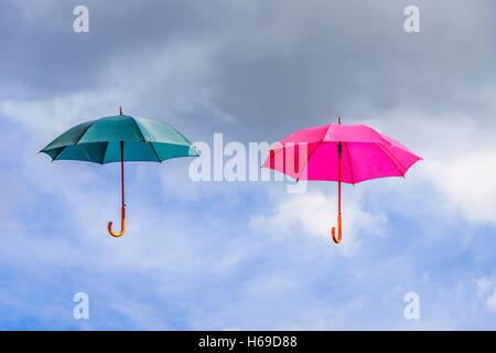Pink and green umbrella or parasols floating suspended in the air under cloudy sky