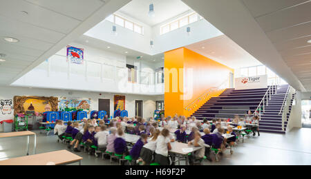 Angled view of central atrium with pupils having lunch. Tiger Primary School, Maidstone, United Kingdom. Architect: - Stock Photo