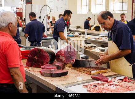 A fish monger cuts slices of tuna fish with a machete knife in the Funchal market hall on the Portuguese island - Stock Photo