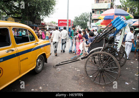 Public Transport  Hand Pulled Rickshaw and Yellow taxi  near Kali temple in Kolkata West Bengal India. - Stock Photo