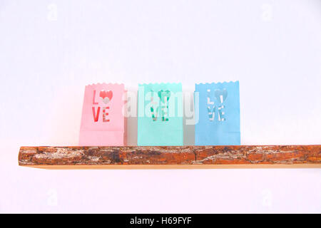 Tealight candle bags love heart colorful wood shelf wall wooden board on a white white pink pink petrol green light - Stock Photo