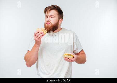 Young bearded man with eyes closed enjoying eating hamburgers isolated on white background - Stock Photo