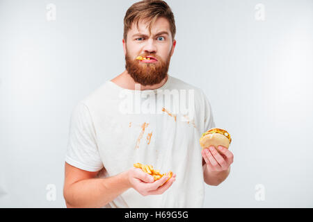 Funny hungry bearded man eating junk food isolated on white background - Stock Photo
