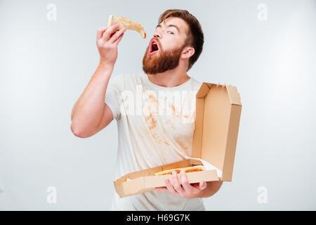 Funny bearded hungry man eating pizza isolated on white background - Stock Photo