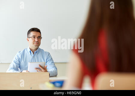 students and teacher with tablet pc at school - Stock Photo