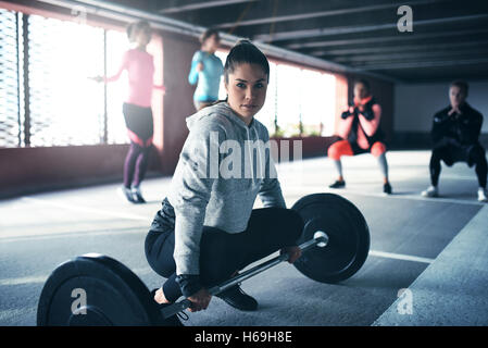 Fit healthy woman exercising, sitting at floor looking at camera, getting ready to lift weight - Stock Photo