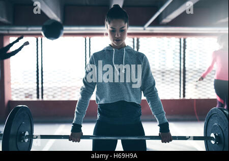 Fit healthy woman lifting a weight barbell, exercising with group of people, looking determined and focused - Stock Photo