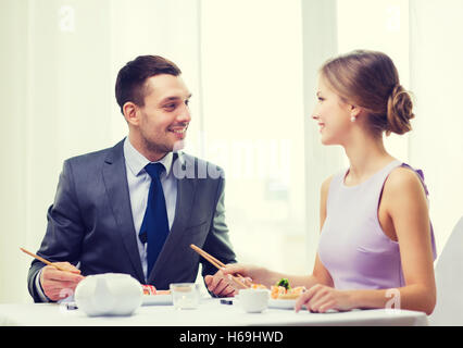 smiling couple eating sushi at restaurant - Stock Photo