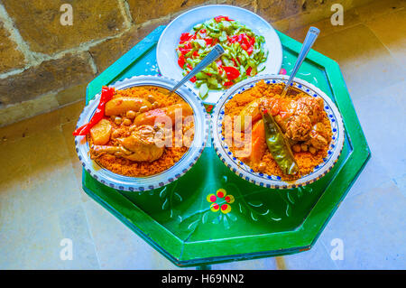 The traditional Tunisian dinner includes vegetable salad and couscous with chicken, Sousse, Tunisia. - Stock Photo