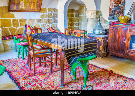 The vintage interior of traditional arabic restaurant decorated wit hold rugs and metal dishware - Stock Photo