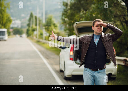 Happy man hitchhiking by a broken car on the road - Stock Photo