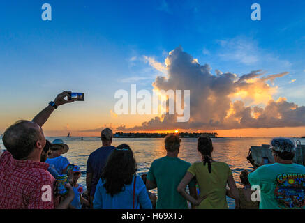 Crazy, joyous sunset celebration scene nightly at Mallory Square in Key West. Visitors gather at sunset to photograph - Stock Photo