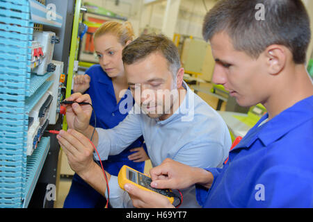 Student electricians using a multi metre - Stock Photo