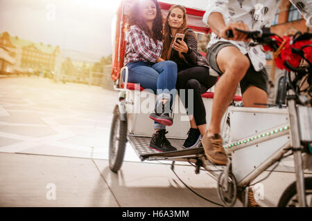 Young women sitting on tricycle and posing for selfie. Female friends enjoying tricycle ride on road and taking self portrait wi