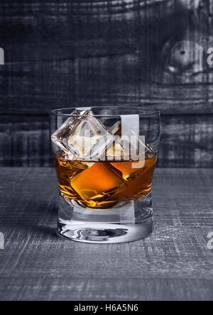 Glass of whiskey with ice cubes on blue wooden background - Stock Photo