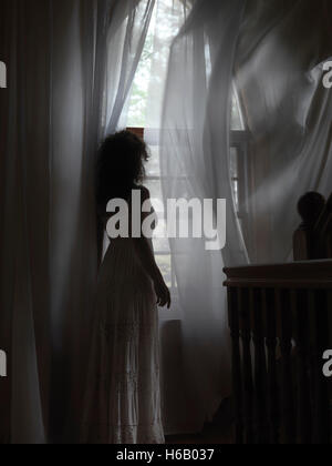 Artistic dramatic photo of a young woman in a dress standing by a window with flying in the wind curtains in a dark - Stock Photo