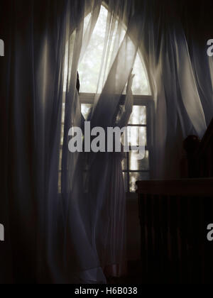 young woman behind curtains artistic dramatic photo of a young woman in a dress standing behind the curtain by a