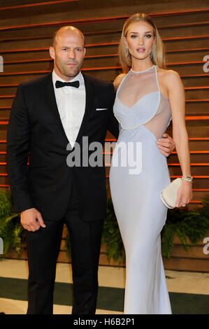 Actor Jason Statham (L) and model Rosie Huntington-Whiteley attend the 2014 Vanity Fair Oscar Party on March 2, - Stock Photo
