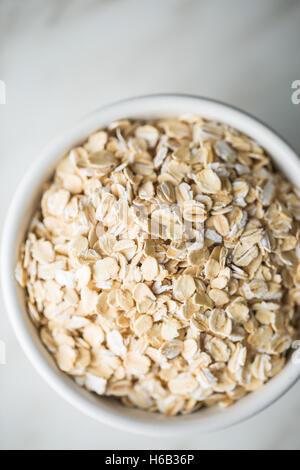 Dry rolled oatmeal in bowl. Top view. - Stock Photo
