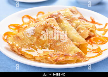 Pancakes with orange syrup on white plate - Stock Photo