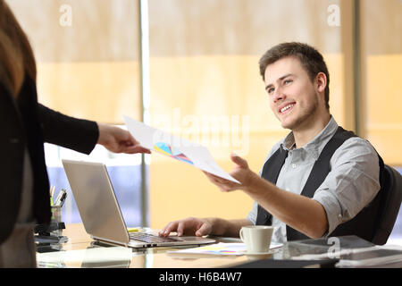 Businesswoman giving a document with growth graphic to a businessman at office. Teamwork concept - Stock Photo