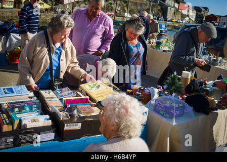 Shoppers finding bargains on a charity fund-raising stall in Mevagissey village Cornwall UK - Stock Photo