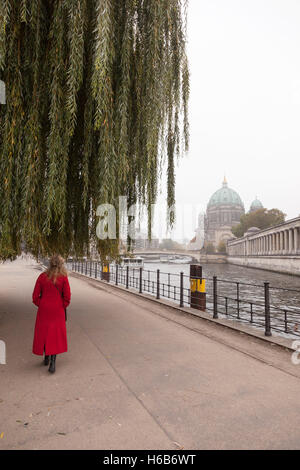 woman in red coat under weeping willow near river spree and berliner dom in berlin - Stock Photo