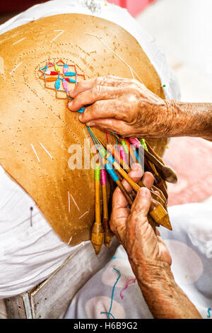 Hands of an artisan woman doing bobbin lace making in Sambaqui, at Santo Antonio de Lisboa district. - Stock Photo