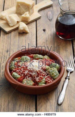 Homemade Italian Gnocchi with tomato sauce and cheese in ceramic bowl rustic kitchen table background - Stock Photo