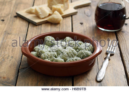 gnocchi with herbs and cheese in ceramic bowl on rustic kitchen table background - Stock Photo