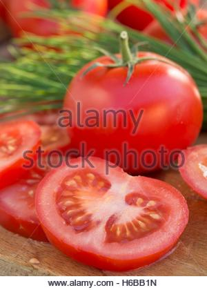 Whole and sliced tomatoes and herbs - Stock Photo