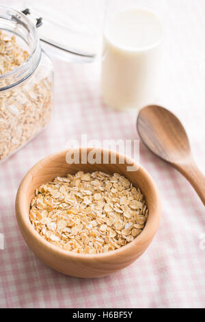 Dry rolled oatmeal in bowl on checkered tablecloth. - Stock Photo