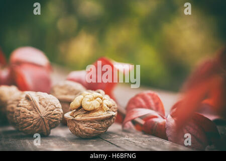 Walnuts on wooden table. Green blurry background with plenty of copy space - Stock Photo